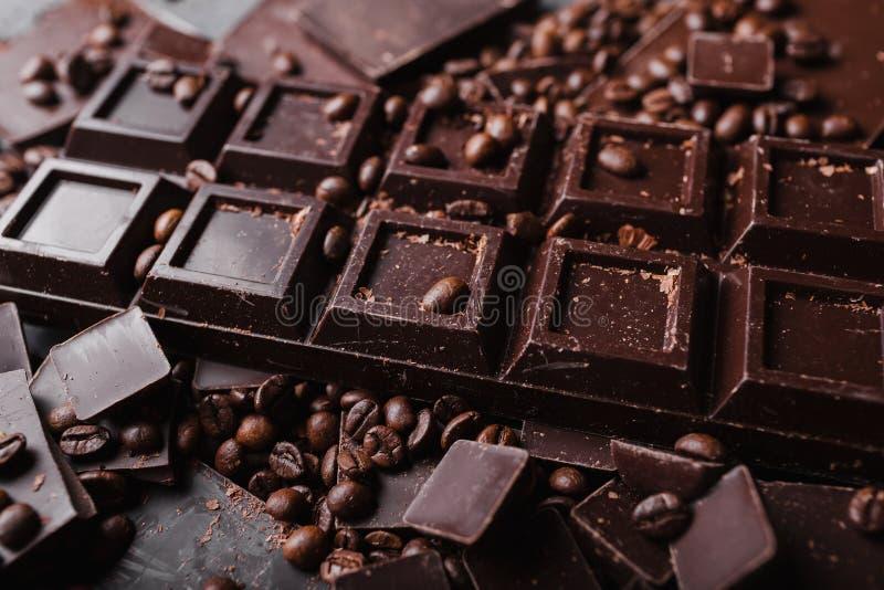 Kaffebönor med chokladmörkerchoklad Brutna skivor av choklad Stycken för chokladstång royaltyfria foton