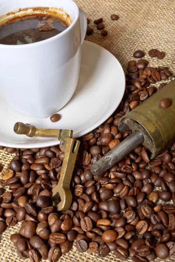 Kaffebönor med kaffekvarnen och koppen kaffe arkivfoto