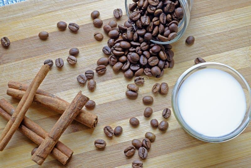 Kaffebönor mjölkar, och kanelbruna pinnar landskap den bästa skörden royaltyfri foto