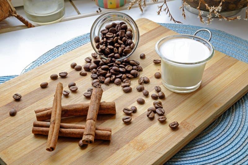 Kaffebönor mjölkar, och kanelbruna pinnar landskap sidosned boll royaltyfri bild