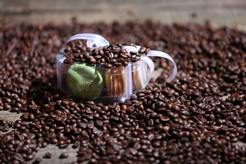Kaffebönor och en ask av macarons royaltyfri foto