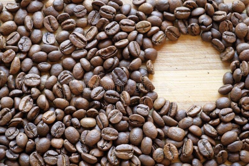 Kaffebönor och en cirkellandskapöverkant royaltyfri foto