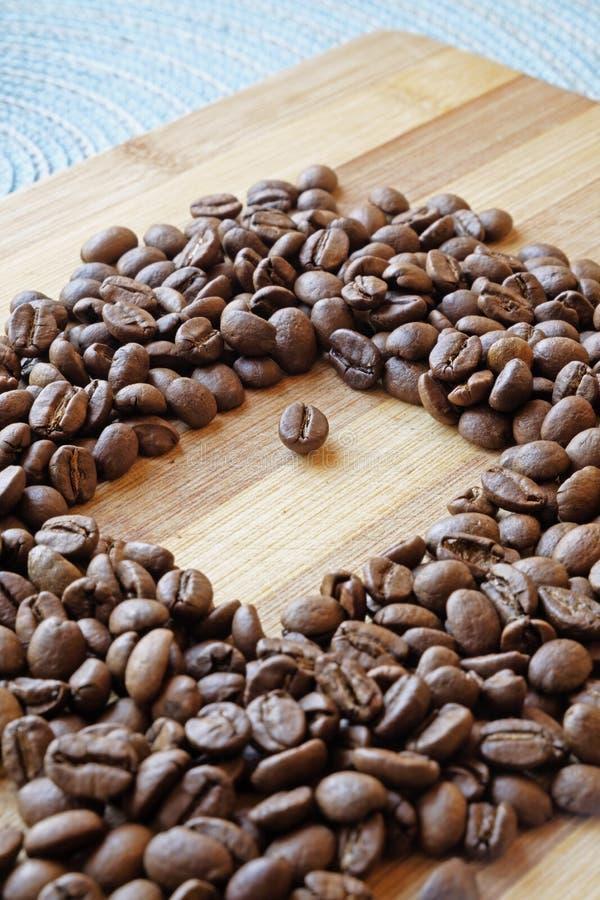 Kaffebönor och en fyrkantig ståendesida royaltyfri fotografi