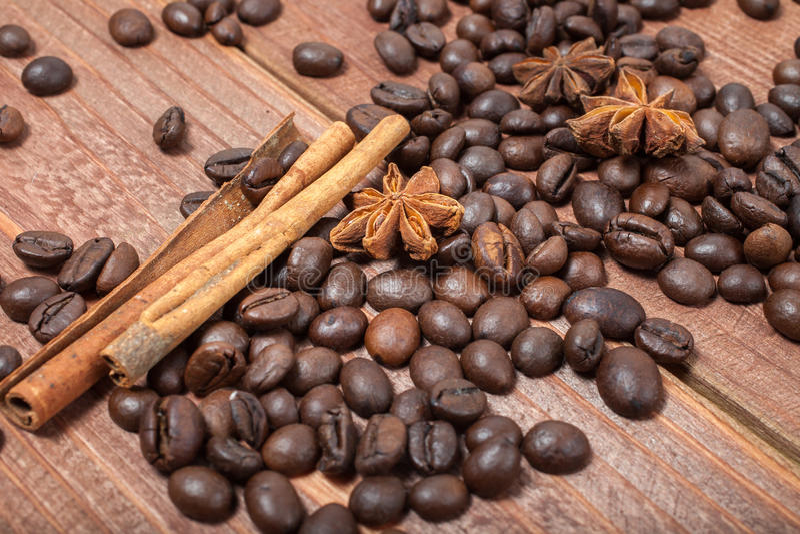 Kaffebönor och kryddor på en trätabell fotografering för bildbyråer