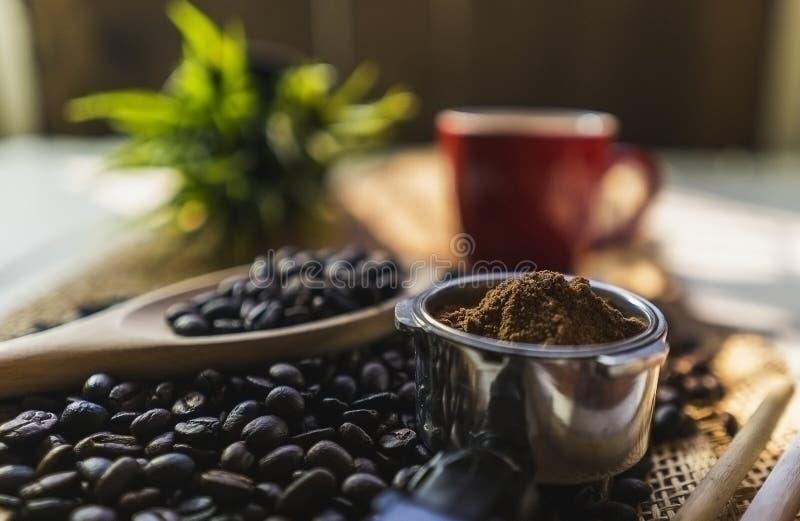 Kaffebönor och röd kaffekopp med säcken på det vita wood skrivbordet arkivbilder