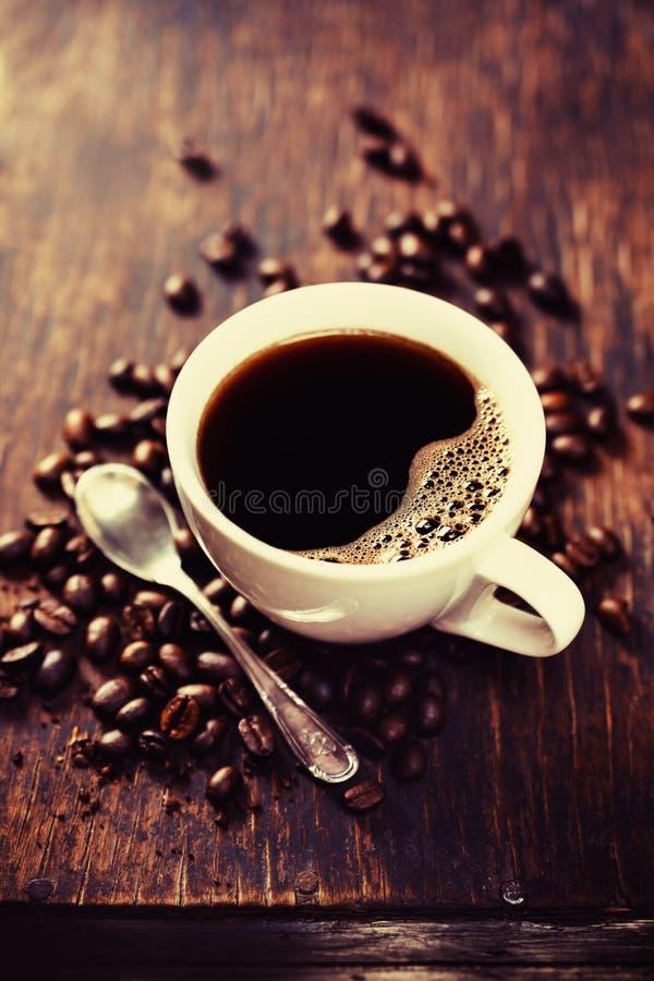 Kaffebönor och sked arkivbilder