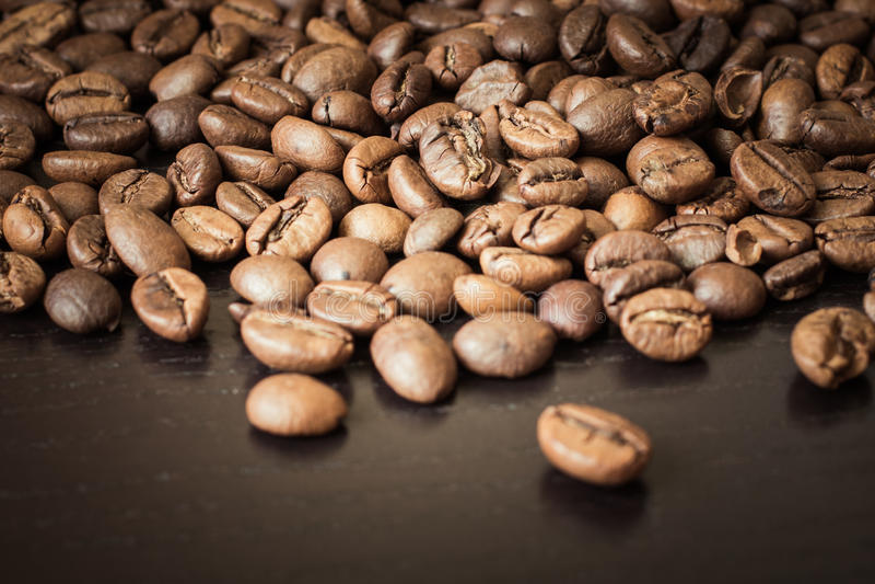 Kaffebönor på en trätabell fotografering för bildbyråer