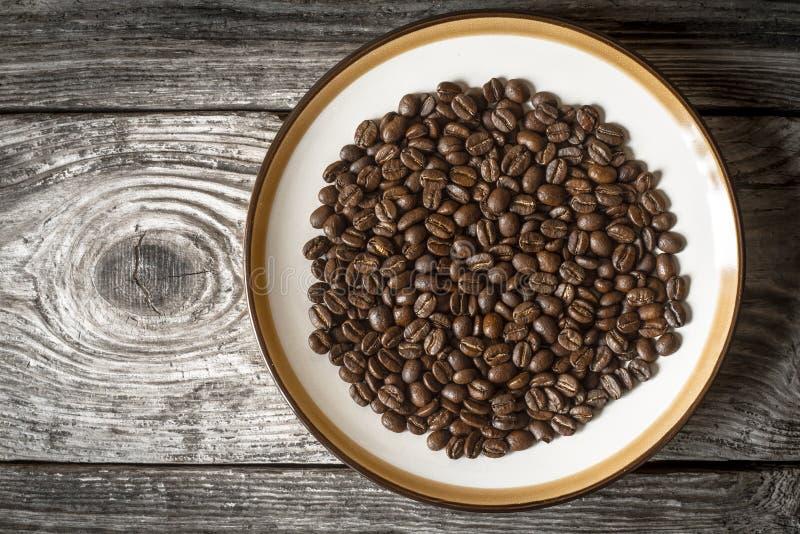 Kaffebönor på plattan på den träbästa sikten för tabell fotografering för bildbyråer
