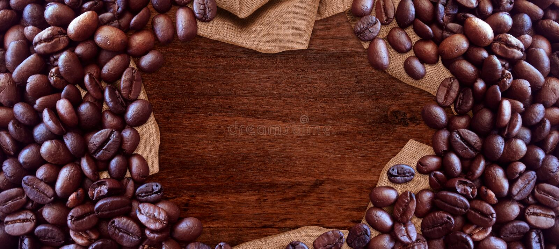 Kaffebönor på stil för tappning för trätabellbakgrund för grafisk design arkivbilder