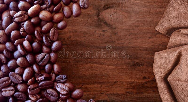 Kaffebönor på stil för träbakgrundstappning för grafisk design arkivfoto