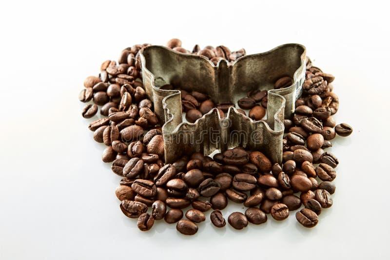Kaffebönor runt om fjärilsform som isoleras på vit arkivfoton