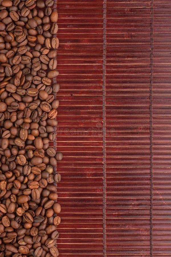 Kaffebönor Som Ligger På En Matt Bambu Arkivbild
