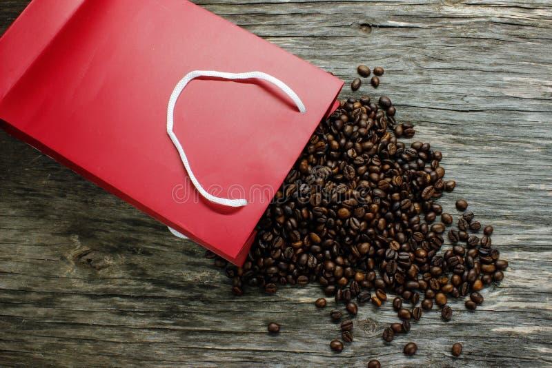 Kaffebönor spriddes från det röda emballaget på en trätabell arkivbild