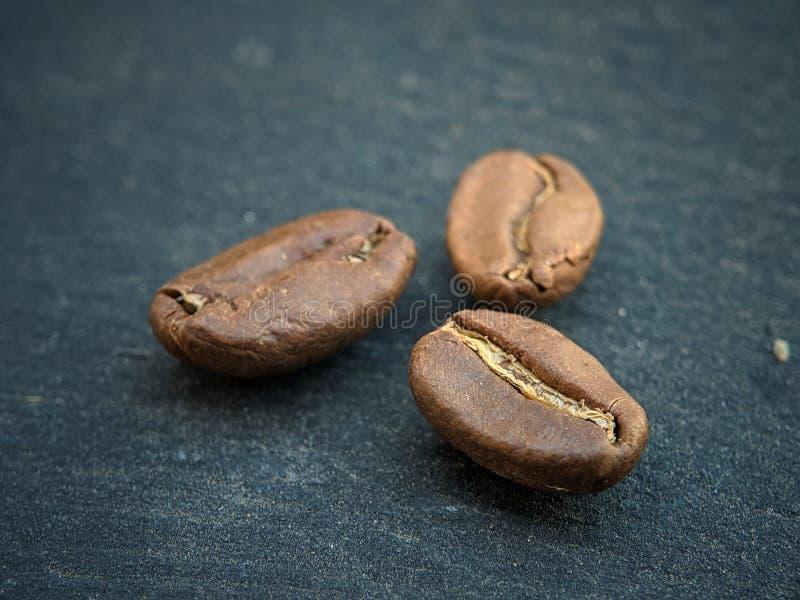Kaffebönor stänger sig upp på svart bakgrundbräde royaltyfri foto