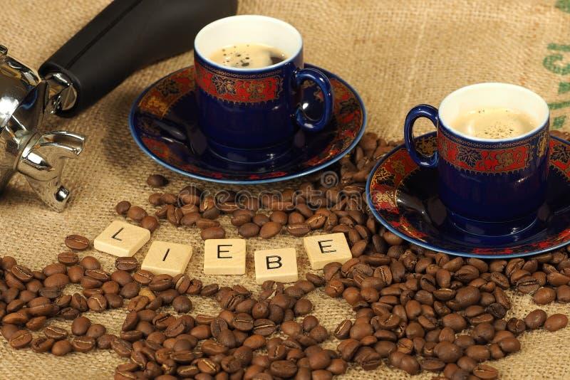 Kaffebönor, två utsmyckade koppar och grupphandtag med bokstäverna Liebe på en hessiansbakgrund arkivfoto