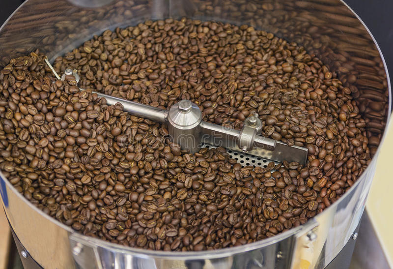 Kaffebönor under den stekheta processen inom hopperen trummar arkivbild