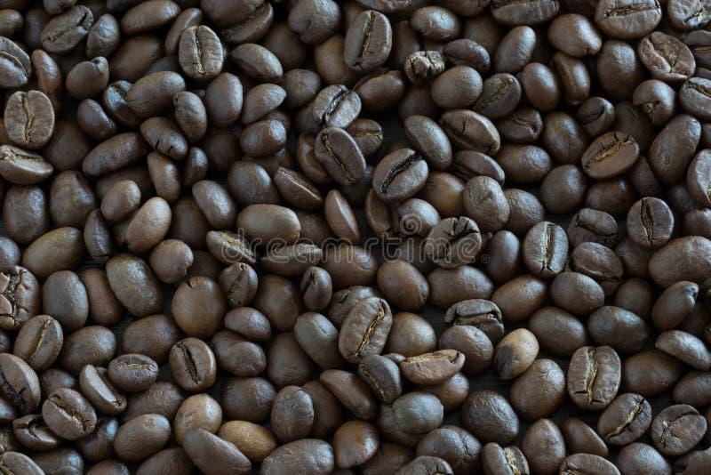 Kaffebönor vid närbild för kaffekorn för bakgrund tätt foto upp arkivfoto
