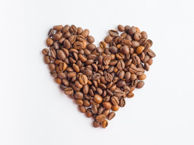 Kaffeb?nor i hj?rta formar p? vit bakgrund royaltyfri fotografi