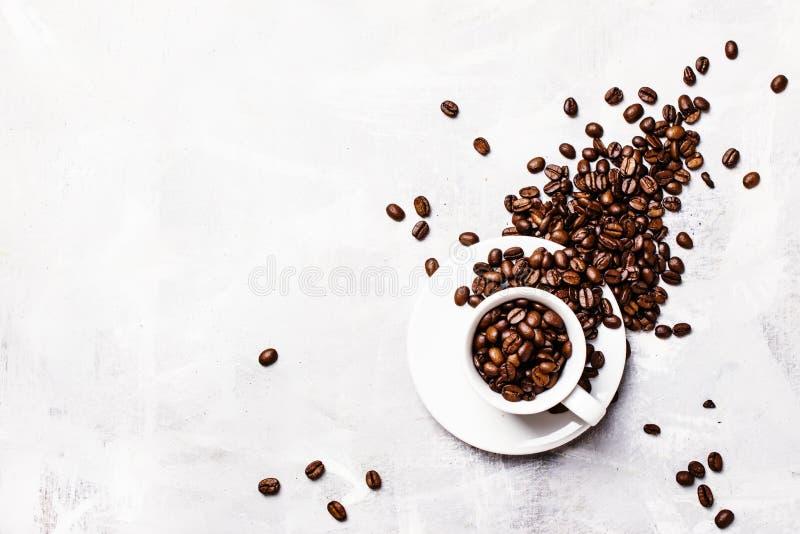 Kaffebakgrund, grillade kaffebönor i en vit kopp, bästa sikt royaltyfri foto