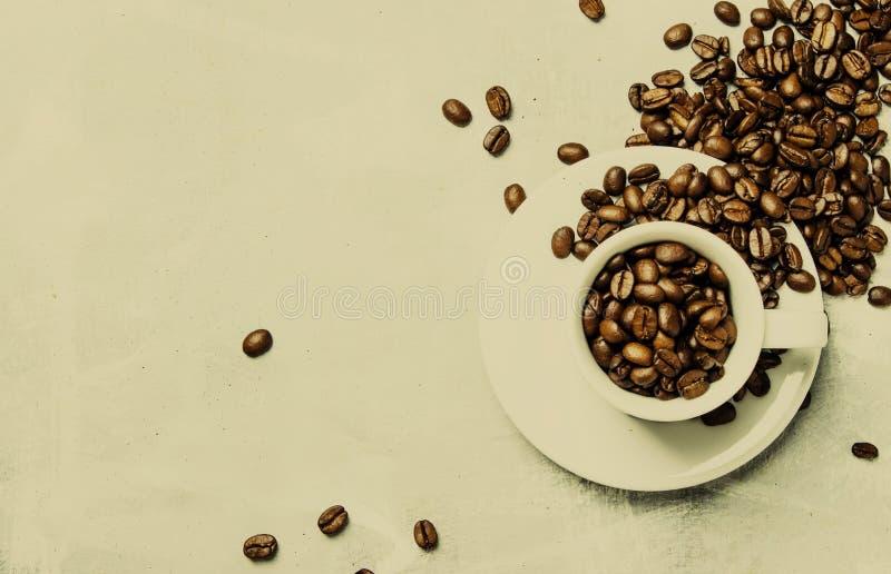 Kaffebakgrund, grillade kaffebönor i en vit kopp, bästa sikt royaltyfria bilder