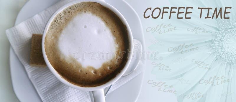 Kaffecappuccino i en vit kopp på en vitt servett och tefat Ställe för text med en stor gerberablomma Top beskådar arkivbild