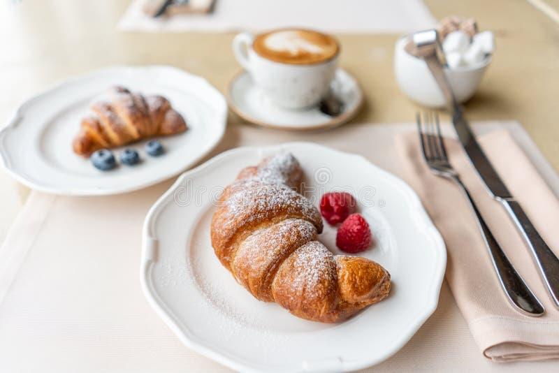 Kaffecappuccino med giffel två på den vita plattan i restaurang Ljus morgonfrukost, nya varma bakelser och royaltyfria foton