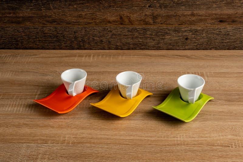 Kaffedishware för orange, gul och grön färg på ett skrivbord arkivfoton