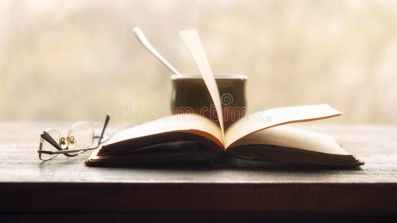 Kaffee-, alte Bücher und Brillen auf der Fensterscheibe lizenzfreies stockfoto