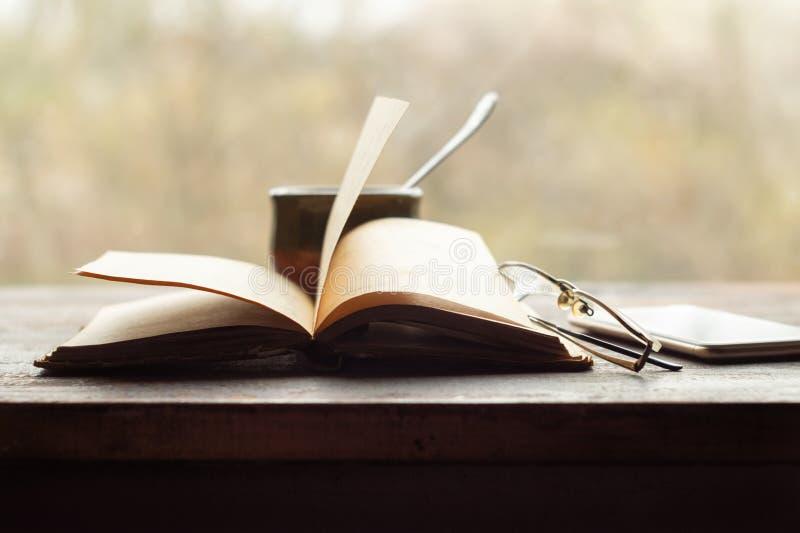 Kaffee, alte Buchbrille und Telefon auf der Fensterscheibe stockfoto