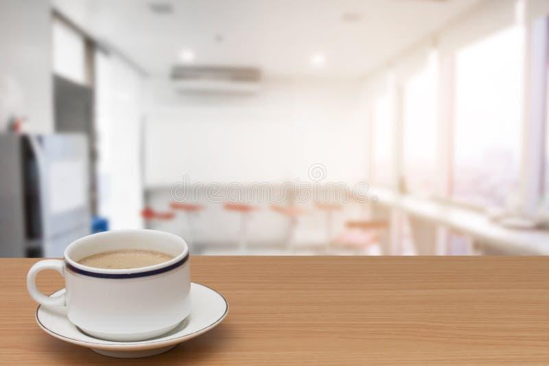Kaffee auf Holztisch mit verwischt vom modernen Kücheninnenraum für Hintergrund lizenzfreie stockbilder