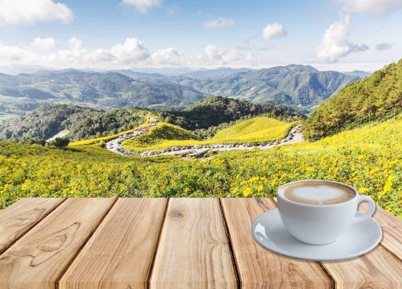Kaffee auf Tabelle am Feld der mexikanischen Sonnenblume lizenzfreie stockfotografie