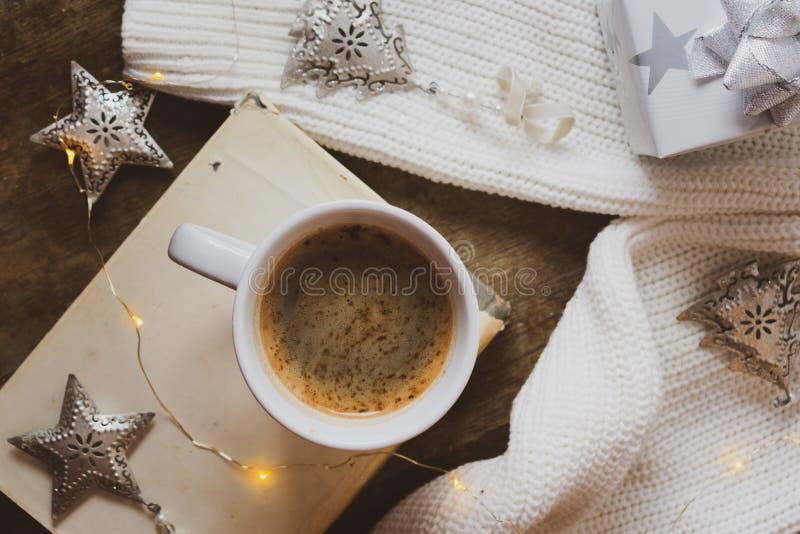Kaffee, Buch, silbernes Weihnachtsgeschenk und Dekorationen auf einem hölzernen Hintergrund stockbild