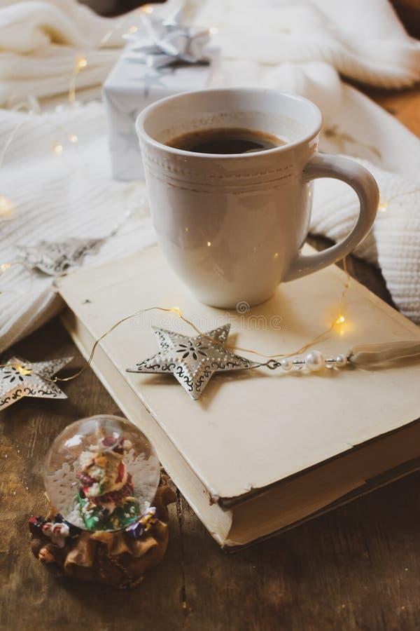 Kaffee, Buch, silbernes Weihnachtsgeschenk und Dekorationen auf einem hölzernen Hintergrund stockfotos