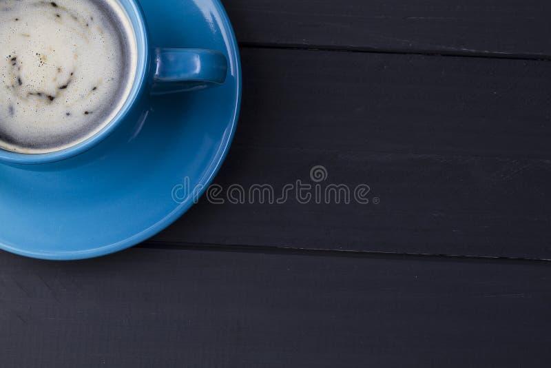 Kaffee in der blauen Schale mit zusammenpassendem Teller auf schwarzem hölzernem Hintergrund lizenzfreie stockbilder