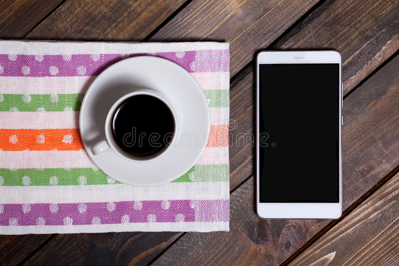 Kaffee in der weißen Schale und im Handy lizenzfreies stockbild