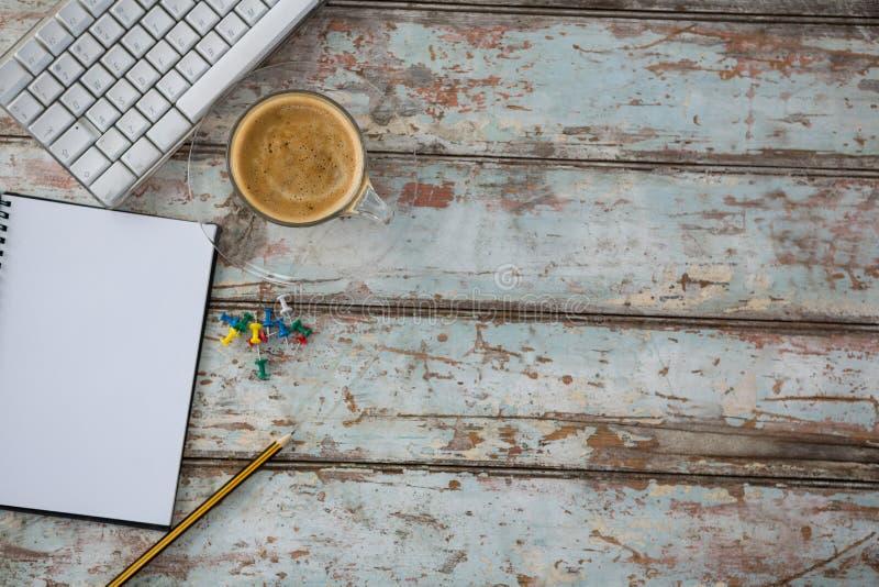 Kaffee, Druckbolzen, Bleistift, Computertastatur und Organisator auf Holztisch lizenzfreie stockfotos