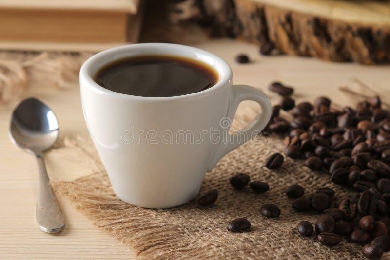 Kaffee in einer weißen Schale und in gebratenen Kaffeebohnen auf einem natürlichen Holztisch Robusta, Arabica stockbilder