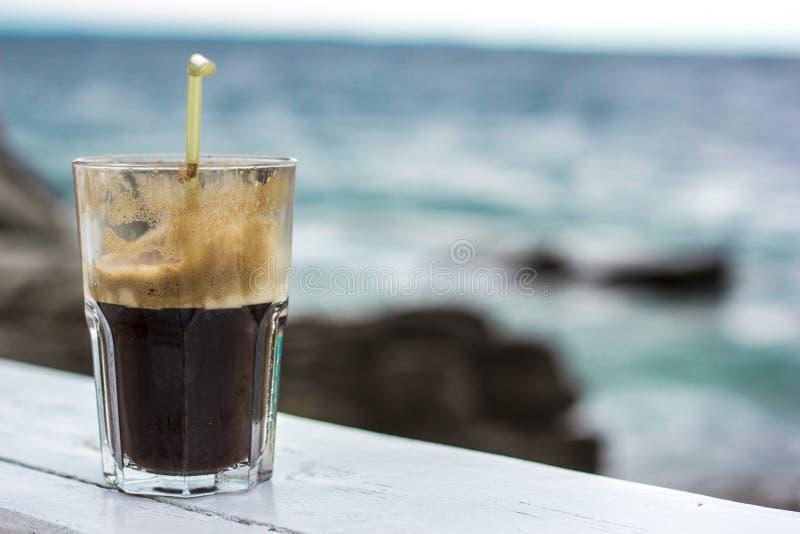 Kaffee Frappe Fredo Iced mit Seehintergrund lizenzfreie stockfotos