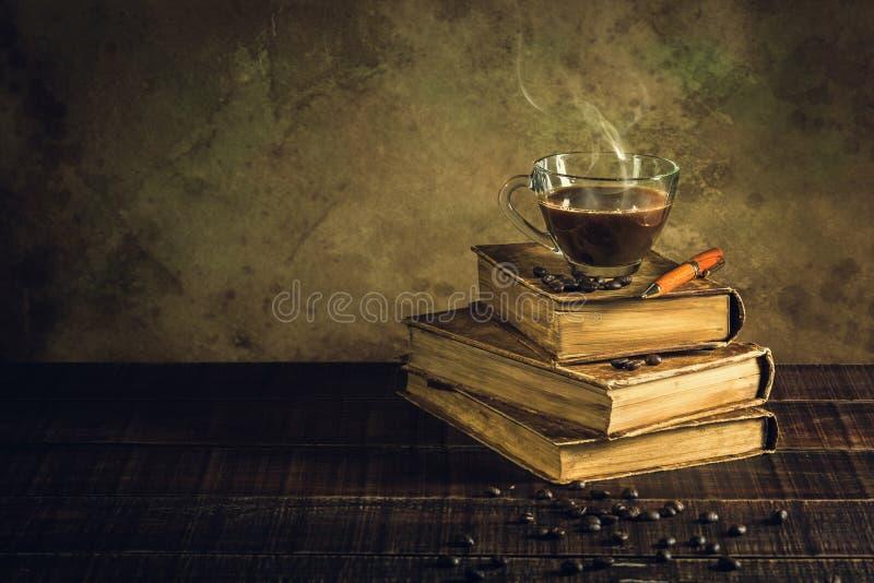 Kaffee im Schalenglas auf alten Büchern und gealtertem Holzfußboden lizenzfreies stockfoto