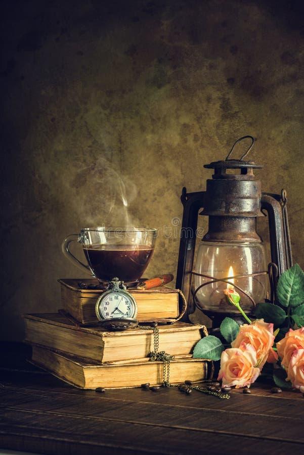 Kaffee im Schalenglas auf alten Büchern und Uhrweinlese mit der Kerosinlampenpetroleumlaterne, die mit weichem Licht des Glühens  lizenzfreie stockfotos