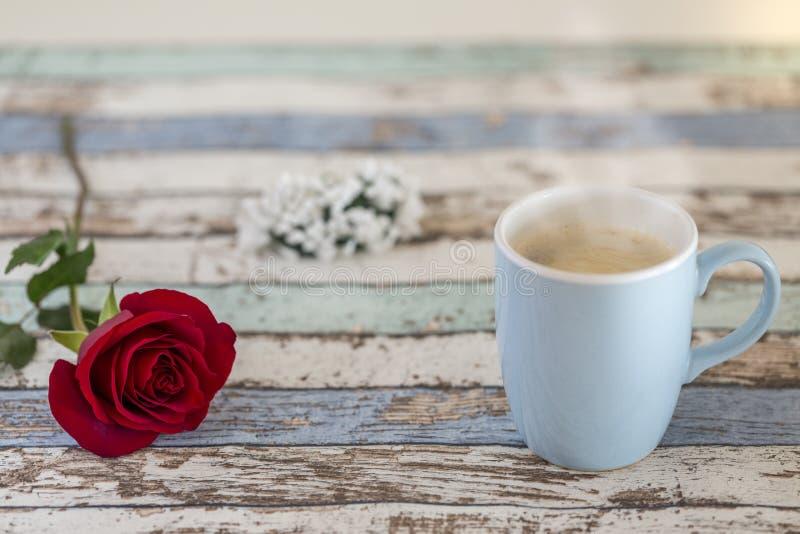 Kaffee im Türkisbecher mit einzelner roter Rose und Blumen auf Tabelle lizenzfreie stockfotografie