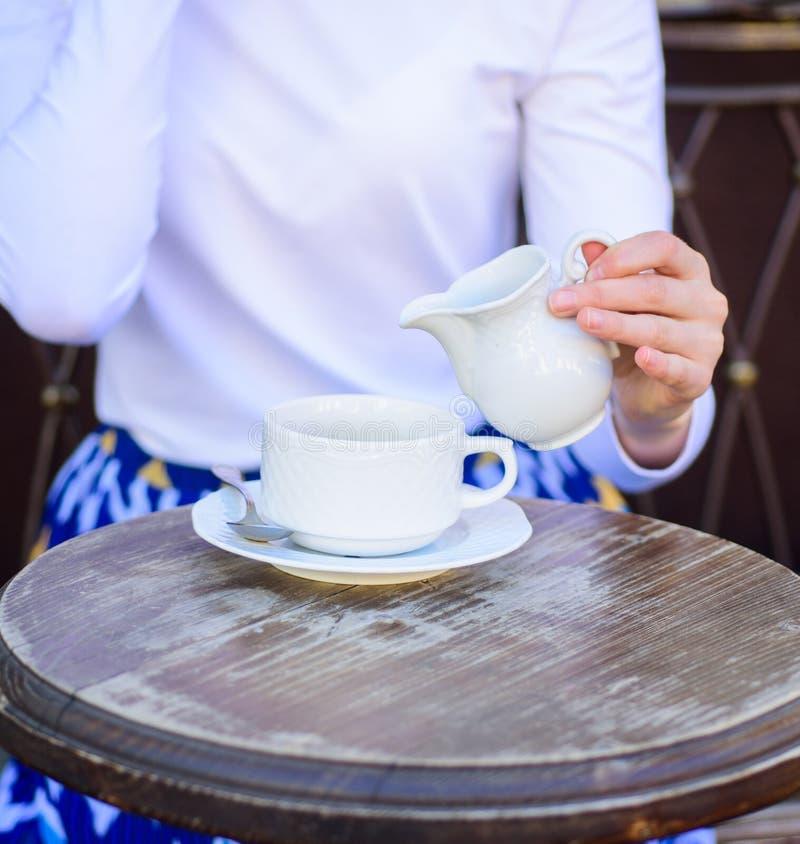 Kaffee immer besser mit Milch Übergeben Sie weibliche hinzufügende Milch zur Caféterrasse des schwarzen Kaffees draußen, Abschlus lizenzfreie stockfotos
