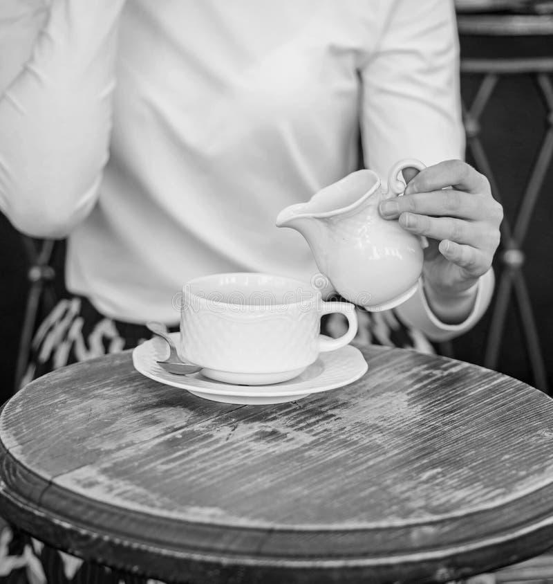 Kaffee immer besser mit Milch Übergeben Sie weibliche hinzufügende Milch zur Caféterrasse des schwarzen Kaffees draußen, Abschlus stockbild