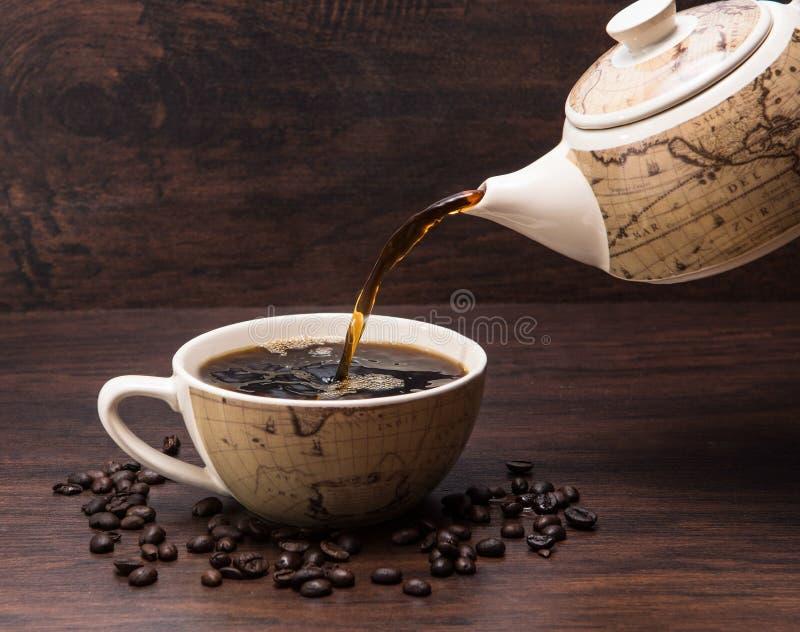 Kaffee läuft in Coffe-Schale mit Coffe-Topf mit Kaffeebohnen aus lizenzfreie stockfotografie