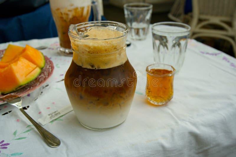 Kaffee Latte, gefrorener Kaffee mit Milch in einem Weckglas und eine Glasschale Ahornsirup setzten sich auf dem Tisch stockfoto