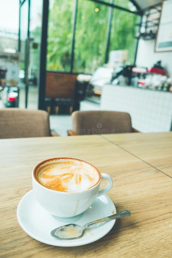 Kaffee Lattekunst mit Laptop auf dem hölzernen Schreibtisch im Kaffeestubeweinlese-Farbton stockfoto