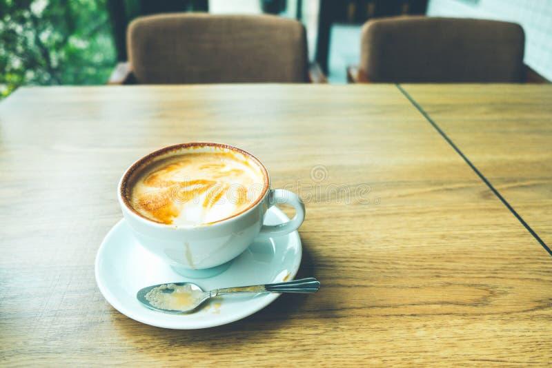 Kaffee Lattekunst mit Laptop auf dem hölzernen Schreibtisch im Kaffeestubeweinlese-Farbton stockbild
