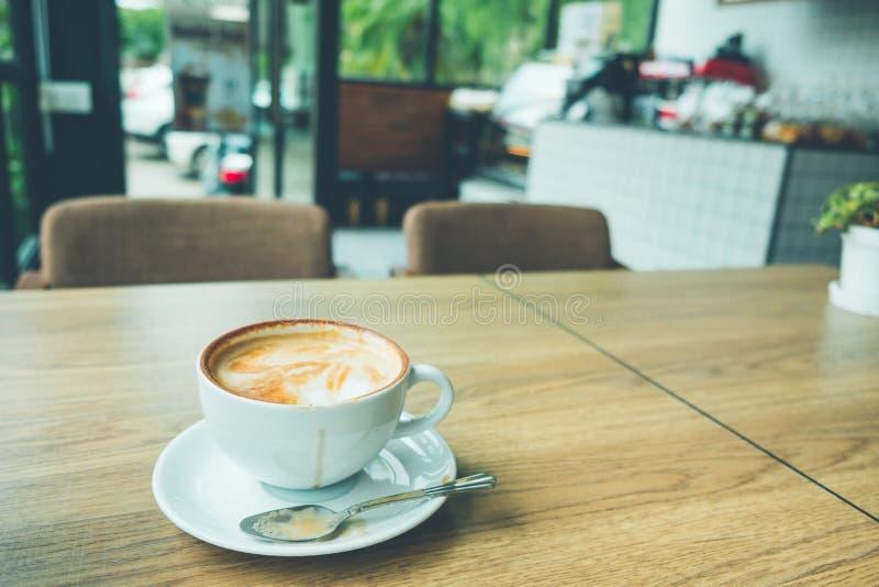 Kaffee Lattekunst mit Laptop auf dem hölzernen Schreibtisch im Kaffeestubeweinlese-Farbton lizenzfreies stockbild