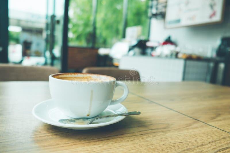 Kaffee Lattekunst mit Laptop auf dem hölzernen Schreibtisch im Kaffeestubeweinlese-Farbton lizenzfreie stockfotos