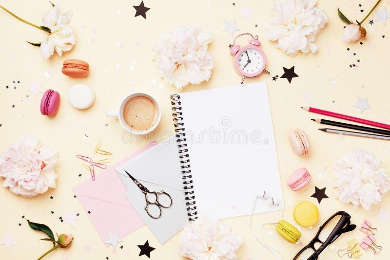 Kaffee, Makronen, Wecker, Bürozubehör, Pfingstrosenblumen und leeres Notizbuch Modefrauenarbeitsschreibtisch Flache Lage stockbilder